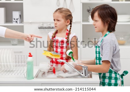 Grumpy kids ordered to do the dishes - by a parent pointed finger - stock photo