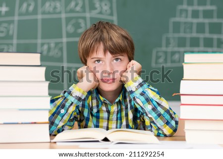 Grumpy little boy in class sitting between two stacks of text books staring morosely up into the air - stock photo