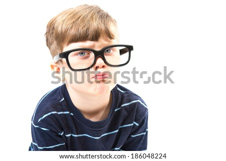 Grumpy, nerdy boy pouts for the camera - stock photo