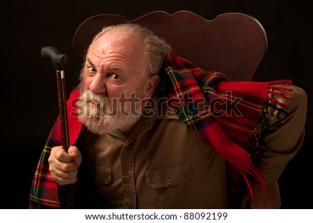 Grumpy old man shakes cane and frowns - stock photo