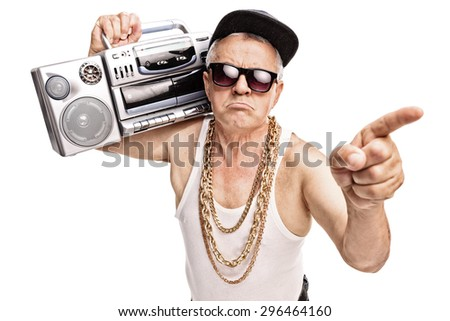 Grumpy senior rapper carrying a ghetto blaster on his shoulder and pointing with his finger isolated on white background - stock photo