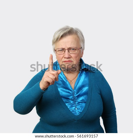 Grumpy senior woman in glasses threatens finger on gray background - grandmother portrait