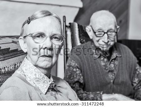Grumpy woman and man looking at camera skeptically - stock photo