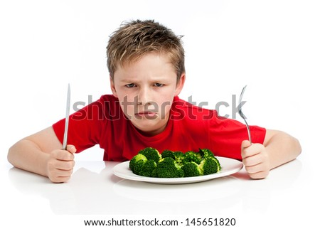 Grumpy young boy with plate of broccoli. Isolated on white background. - stock photo