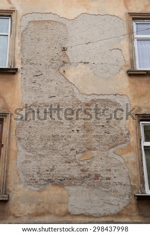 Grunge aged street wall of the old house with cracks . Textured rusty old-fashioned background with space for your design. - stock photo