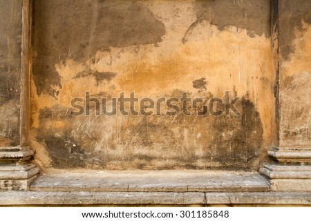 Grunge aged street wall with columns of the old house with cracks . Textured rusty old-fashioned background with space for your design.  - stock photo