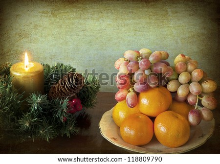 Grunge and simple Christmas: wreath with golden candle and a dish of mandarins and grapes - stock photo