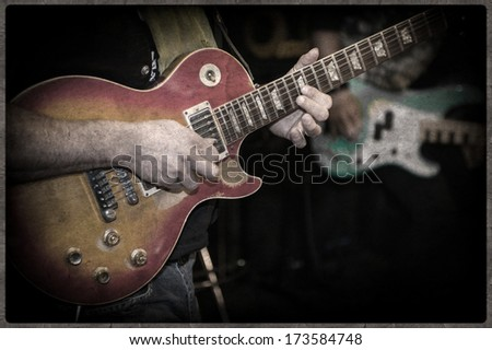 Grunge and Vintage,, defocus, guitarist during the live performance on stage - stock photo