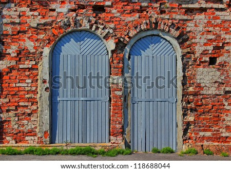 Grunge background of two arch wooden doors and red ancient bricklaying of the 18th eyelid. - stock photo