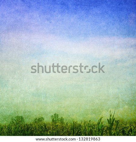 Grunge background with green field and blue sky. Faded central area for copy space.