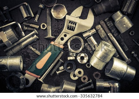 Grunge background with tools and bolts. Adjustable wrench, screws, nuts. Toned.