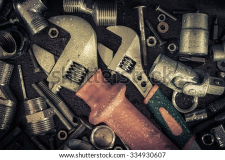 Grunge background with wet tools and bolts. Adjustable wrench, screws, nuts. Toned.