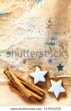 Grunge Christmas background with star-shaped cookies and stick cinnamon on aged stained crumpled paper strewn with small seeds with copyspace - stock photo