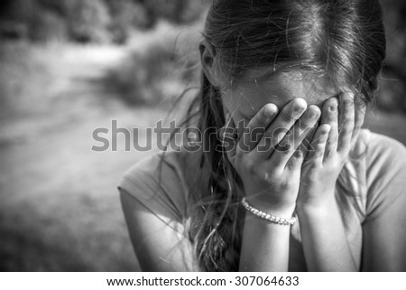 Grunge close-up portrait of a girl crying and covering her face