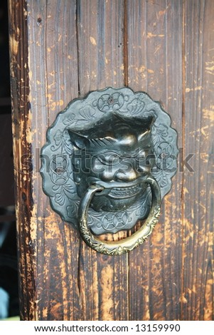 Grunge door with antique Chinese lion knob - stock photo