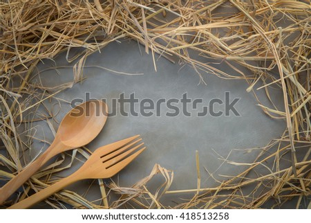 grunge frame made of straw with wooden spoon and fork on grey background - stock photo