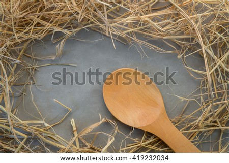 grunge frame made of straw with wooden spoon on grey background - stock photo