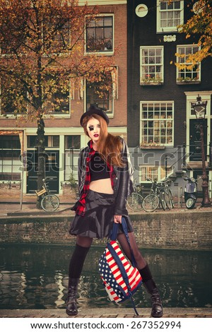 grunge girl with a backpack in the style of an American flag and wearing a hat posing on the streets of Amsterdam - stock photo