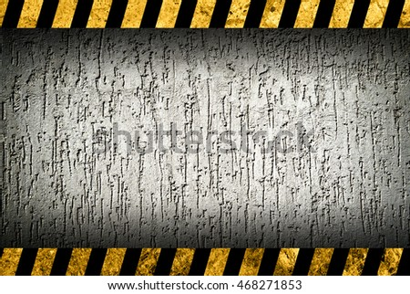 Grunge grey wall background with black and yellow warning stripes