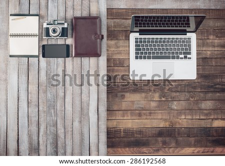 Grunge hipster wooden desktop with vintage camera, computer, organizer, mobile phone and notebook, blank copy space - stock photo