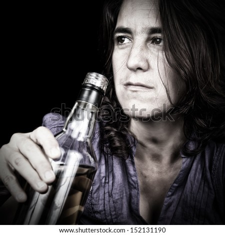 Grunge image of a drunk latin woman drinking from a whisky bottle (on a black background)