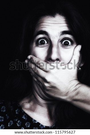 Grunge image of a frightened woman covering her mouth useful to illustrate gender violence or discrimination (on a black background)