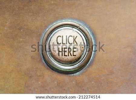 Grunge image of an old button - click here - stock photo