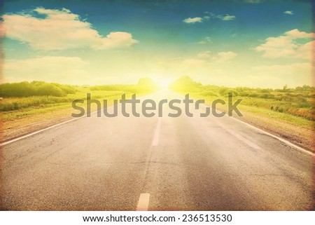 Grunge image of country asphalt road at sunset.  - stock photo