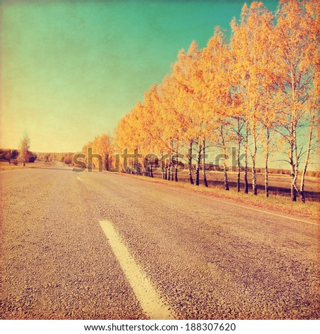 Grunge image of empty country road in autumn time. - stock photo