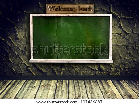 grunge interior with blackboard on cracked wall