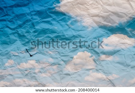 Grunge paper texture. with s white puffy clouds and flying bird - stock photo