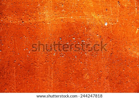 Grunge plaster cement or concrete wall texture orange color with scratches - stock photo
