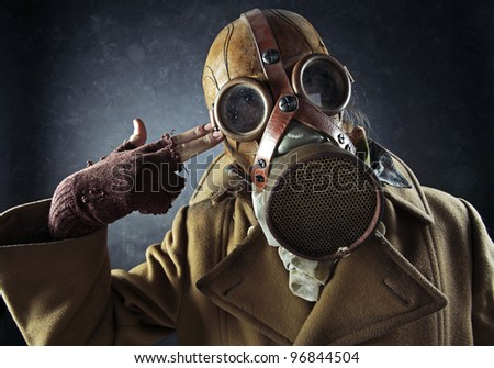 grunge portrait man in gas mask pointing hand gun at his own head, suicide