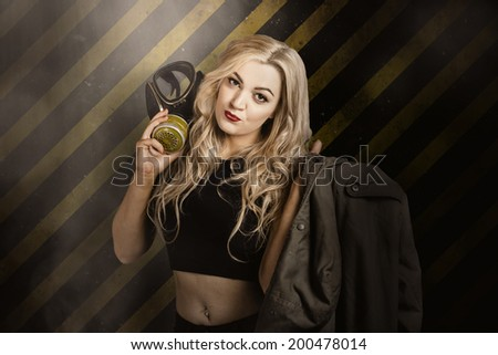 Grunge portrait of a blond pin up woman holding gas mask on yellow and black caution background. Nuclear danger - stock photo