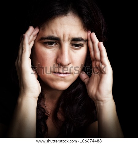 Grunge portrait of a depressed and sad hispanic woman with her hands touching her forehead isolated on a black background - stock photo