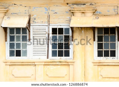 Grunge ramshackle windows with broken glass on yellow wall - stock photo