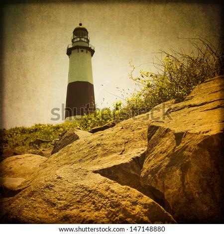 Grunge retro-style Montauk Lighthouse and rocks - stock photo