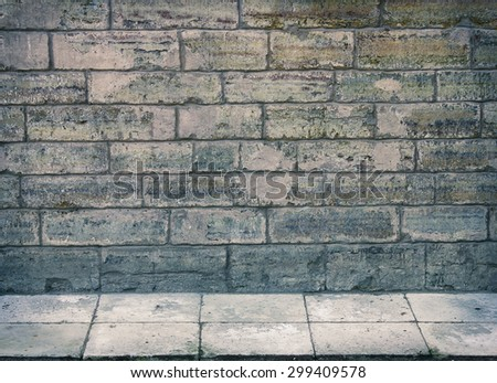 Grunge room interior with stone wall and tiled floor - stock photo