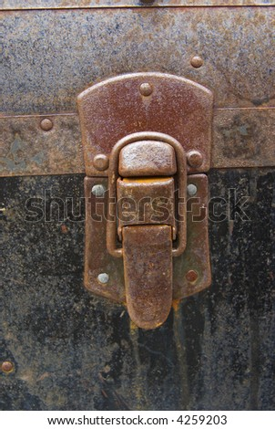 Grunge rusty latch on antique metal trunk - closeup