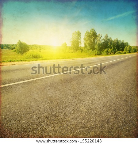 Grunge style image of country asphalt road at sunset.
