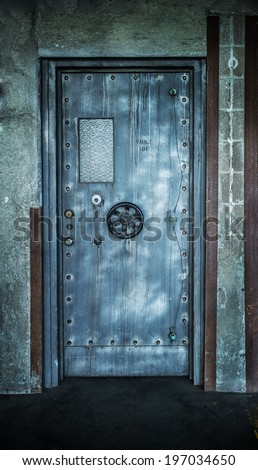Grunge style image of old metal door background with vault lock. - stock photo