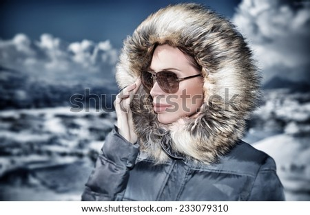 Grunge style photo of luxury woman portrait in wintertime outdoors, wearing stylish sunglasses and warm coat with furry hood and looking away, fashionable winter style concept - stock photo