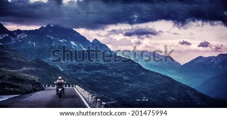 Grunge style photo of motorcyclist on mountainous highway, riding in the evening in overcast weather, traveling along European mountains  - stock photo