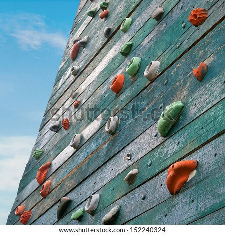 Grunge surface of an artificial rock climbing wall with toe and hand hold studs. - stock photo