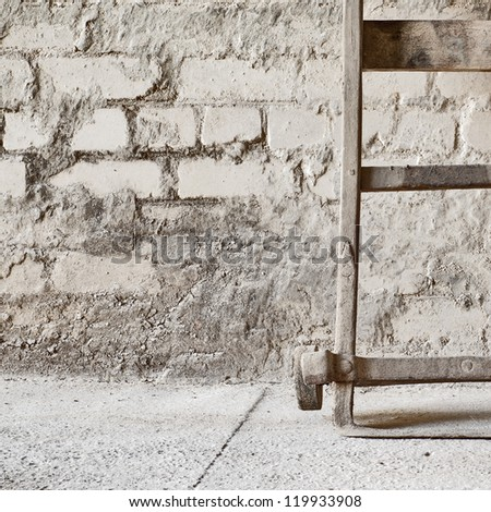 grunge wall,  vintage two wheels barrow for carrying grain sacks background