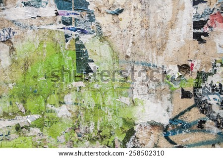 Grunge weathered urban wall with peeled residues of old posters as background - stock photo