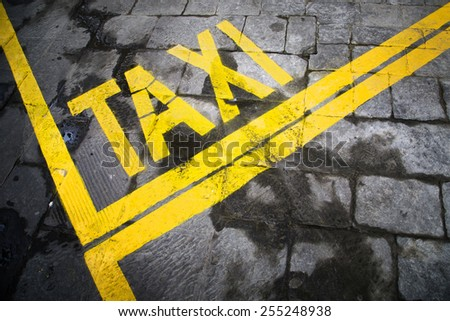 Grunge yellow color taxi sign station painted on the stone street floor. - stock photo