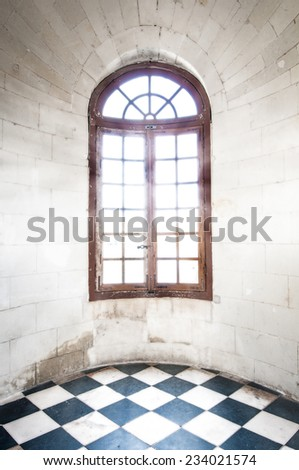 Grungy arched window with bright sunlight inside old building made of white stone with black-and-white tile on floor. Room is round and empty. Historic castle or fortress indoors. - stock photo