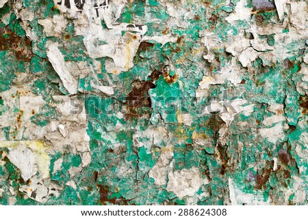 Grungy close-up of old flaking paper and rust stains on a green colored advertising board - stock photo