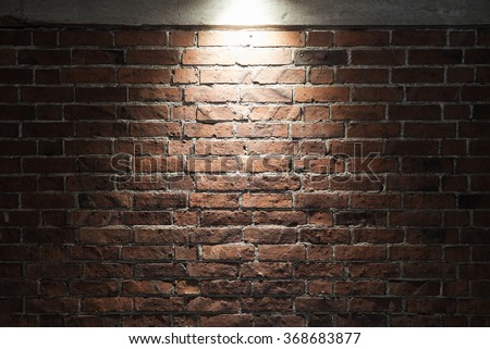 Grungy dark red brick wall with spotlight, background photo texture